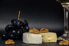 Närbilden högg av camembertost, muttrar och söta blåa druvor på bakgrunden av ett exponeringsglas av vitt torrt vin royaltyfria foton