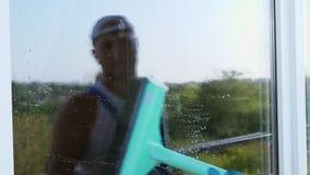 Närbilden i fönsterexponeringsglaset reflekteras en man, arbetare av lokalvårdservice, i blåa overaller och i ett lock, blaser stock video