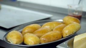 Närbilden kocken, kockhänder i handskar lägger ut nytt lagade mat pajer på ett magasin för att tjäna som till en till salu kafete stock video