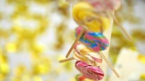 Närbilden mång--färgade klubbor, sötsaker, på bakgrunden av guld- blänker från smällare, festligt glitter lager videofilmer