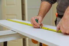 Närbilden mannen mäter ett träbräde med en linjal och markerar med blyertspennan royaltyfri foto
