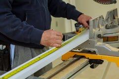 Närbilden mannen mäter ett träbräde med en linjal och markerar med blyertspennan arkivfoton
