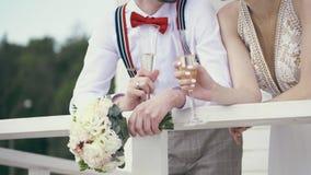 Närbilden nygifta personer rymmer champagneexponeringsglas och en gifta sig bukett stock video