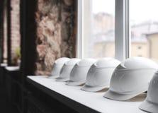 Närbilden på de vita konstruktionshjälmarna ligger på fönsterbrädan i rad inom byggnaden under konstruktion Arkivfoton