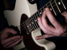 Närbilden sköt av en gitarrist som spelar på en elektrisk gitarr arkivbilder