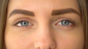 Närbilden sköt av en kvinna som öppnar hennes blåa ögon med ljust dagsmink och fokuserar dem lager videofilmer