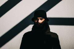 Närbilden sköt av en stilig ung man som framme står av en grå vägg Fotografering för Bildbyråer