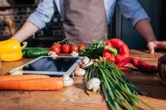 närbilden sköt av matlagning för ung man med minnestavlan arkivfoton