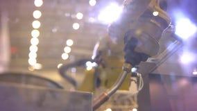 Närbilden som sköts av rotering, leda i rör den automatiska robotic armen i process på utställningbakgrund stock video