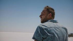 Närbilden som sköts av ung trött man i tillfällig kläder, förlorade och att se omkring i mitt av varmt torrt saltar sjööknen Utah stock video