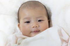 Närbilden som två gamla nyfödda asiatiska gulligt för månad behandla som ett barn leende, vilar mummel Royaltyfri Foto