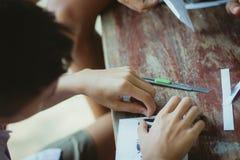 Närbilden till händer av studenter klipper tryck och klistermärkear royaltyfri bild