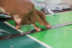 Närbilden till händer av studenter klipper tryck och klistermärkear Arkivfoto