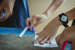 Närbilden till händer av studenter klipper tryck och klistermärkear Arkivfoton