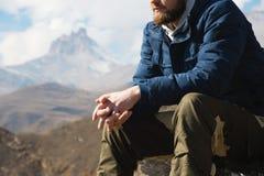 Närbilden utan en framsidasammanträdehipster på en sten som är hög i bergen mot bakgrunden av epos, vaggar _ arkivfoto