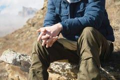 Närbilden utan en framsidasammanträdehipster på en sten som är hög i bergen mot bakgrunden av epos, vaggar _ fotografering för bildbyråer