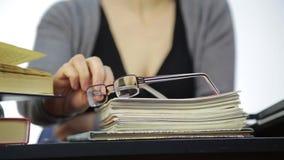 Närbildexponeringsglas på skrivböcker, lärare arbetar utan exponeringsglas efter visionkorrigering arkivfilmer