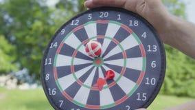 Närbildfaderhänder som rymmer pilar medan hans son som kastar pilar och bollen på en magnet i cirklarna Familjfritid stock video
