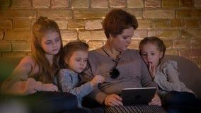 Närbildfamiljstående av den caucasian modern och döttrar som håller ögonen på in i minnestavlan med stort intresse i mysigt hem stock video