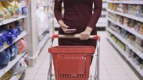 Närbildflickahänder rullar spårvagnen i handla golv av supermarket och brukstelefonen lager videofilmer
