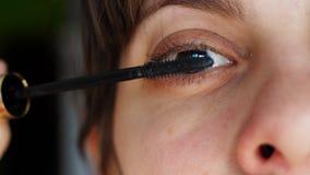 Närbildflickan korrigerar makeup Flickan målar ögonfransmascara arkivfilmer