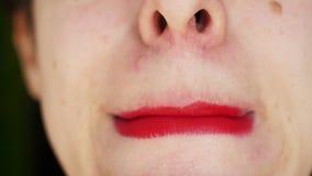 Närbildflickan korrigerar makeup Kvinnan torkar röd läppstift runt om kanter lager videofilmer
