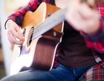 Närbildflickan spelar den akustiska gitarren Fotografering för Bildbyråer