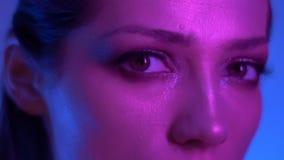 Närbildfors av den futuristiska modemodellen i färgrika neonljus som fast håller ögonen på in i kamera i studio lager videofilmer