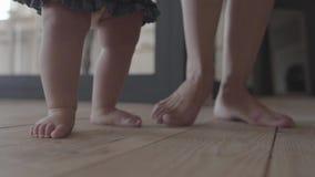 Närbildfoten av en ung kvinna och hennes behandla som ett barn att stå på golvet hemma Begrepp av en lycklig familj, ett barn, fö stock video