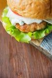 Närbildfoto av den hem- gjorda hamburgaren med nötkött, löken, tomaten, grönsallat, ost och kryddor Ny hamburgarecloseup på Arkivfoton