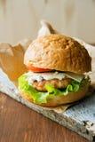 Närbildfoto av den hem- gjorda hamburgaren med nötkött, löken, tomaten, grönsallat, ost och kryddor Ny hamburgarecloseup på Royaltyfria Foton