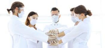 Närbildfoto av doktorer som staplar handen med Coworkers Arkivbild