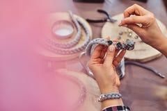 Närbildfoto av en kvinnas händer som gör handgjorda halsband arkivbilder
