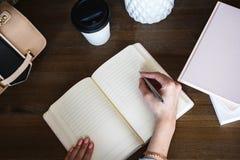 Närbildfoto av scheduleranteckningsboken på en trätabell Den kvinnliga handen skriver på papper Arkivbild