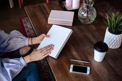 Närbildfoto av scheduleranteckningsboken på en trätabell Den kvinnliga handen skriver på papper Arkivbilder