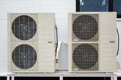 Närbildfoto av två utomhus- enheter av luftkonditioneringsapparater som framme står på jordningen av fasaden av den moderna byggn Arkivfoton