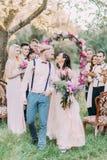 Närbildfotoet av den älskvärda bröllopceremonin i det soliga trät De le nygift personparen på bakgrunden av Royaltyfri Foto