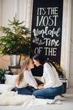 Närbildfotoet av lilla flickan i stucken tröja kysser hennes moder, medan sitta på soffan på jul arkivbilder