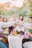 Närbildfotoet av nygifta personerna och gästerna som klirrar deras exponeringsglas och mycket sitter på tabellen av läcker mat fotografering för bildbyråer