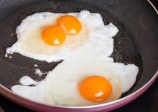 Närbildfotoet av två förvanskade ägg i panna Royaltyfri Bild