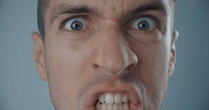 Närbildframsida av den ilskna mannen som skriker mot vit bakgrund arkivfilmer