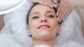 Närbildframsida av den lyckliga härliga kvinnan som kopplar av och tycker om massage på den moderna brunnsortsalongen stock video