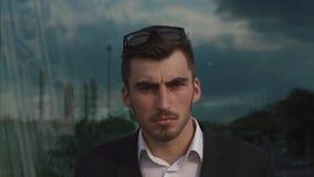 Närbildframsida av den manliga modellen för säker stilig elegant affärsman som stirrar på kameran i exponeringsglas Seamless text stock video