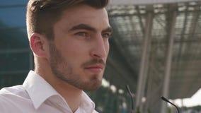 Närbildframsida av den manliga modellen för stiligt mode som tar på hans solglasögon och blickar till kameran Stads- stadsbakgrun arkivfilmer