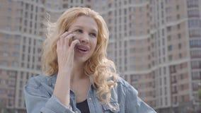 Närbildframsida av den nätta le säkra blonda kvinnan som framme talar vid mobiltelefonen av skyskrapan stads- livsstil lager videofilmer