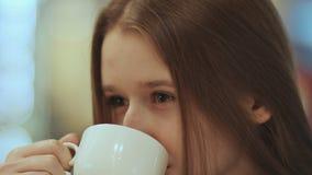 Närbildframsida av den unga härliga skolflickan som dricker kaffe från en kopp arkivfilmer