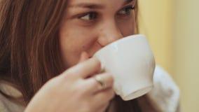 Närbildframsida av den unga härliga skolflickan som dricker kaffe från en kopp lager videofilmer