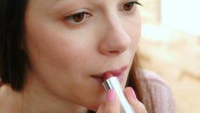 Närbildframsida av en kvinna som sätter ljus läppstift på hennes kanter stock video
