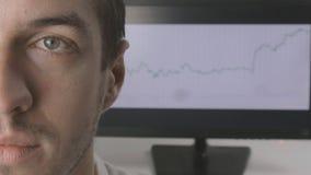 Närbildframsida av en ung affärsman mot bakgrunden av handelschemat på bildskärmen lager videofilmer