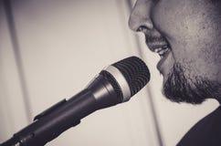 Närbildframsida av sångaren med mikrofonen och att sjunga på svartvit bakgrund royaltyfri foto